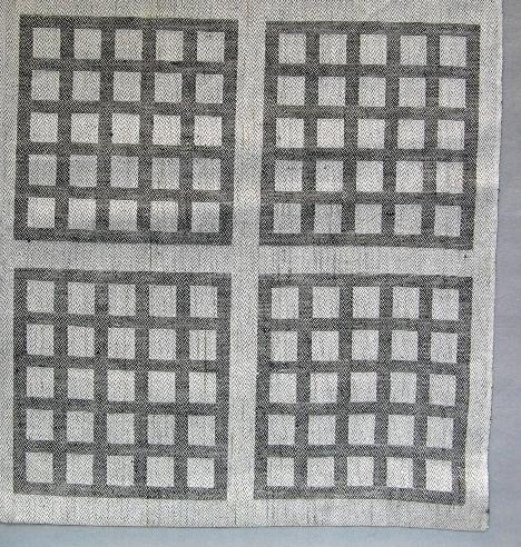 """Duk vävd i 12 skaft dräll med mönster liknande ventilgaller. Varpen är halvblekt i tunt tvåtrådigt lingarn. Inslaget är svart entrådigt lingarn. Mönsterfiguren är kvadratisk med fem gånger fem små kvadrater och liknar ett ventilgaller.   I ett hörn är en pappersetikett fastknuten med texten:  """"Ventil"""" 12 sk. dräll, MATERIAL Ling 28/2 Ling.16/1, FORM/URSPRUNG Ann-Marie Nilsson PRIS ej till salu"""". På andra sidan av etiketten är en spånfågel och texten """"LÄNSHEMSLÖJDEN SKARABORG SKÖVDE"""". På ett bomullsband står det R1:2. I den andra kortsidan är duken märkt med ett bomullsband med texten: """"VENTIL""""Ann-Mari Nilsson"""".  Duken med modellnamn Ventil är formgiven av Ann-Mari Nilsson och tillverkad av Länshemslöjden Skaraborg. Den finns med  på sidan 26-27 i vävboken Inredningsvävar av Ann-Mari Nilsson i samarbete med Länshemslöjden Skaraborg från 1987, ICA Bokförlag. Se även inv.nr. 0001-0008,0010-0040."""
