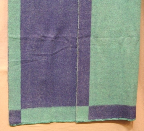 """Filt vävd i inslagsförstärkt tuskaft i smidig halvylle kvalitet. Det är blekt tvåtrådigt bomullsgarn i varpen och blått (blålila) och blågrönt (turkost) tvåtrådigt ullgarn, filtgarn, i inslaget. Filten är dubbelsidig. På ena sidan dominerar den blålila färgen och den turkosa bildar en ram och tvärt om på andra sidan.  Den ena kortsidan är virkad med blålila garn och den andra med turkost. En vit pappersetikett med texten """"DUBBEL"""" är fastklistrad i ett av hörnen.  Filten är märkt med R28:1 på ett vitt bomullsband.  Se även inv.nr 0028:2 Vävprov till filt Dubbel.  Filt med modellnamn Dubbel är formgiven av Ann-Mari Nilsson och tillverkad av Länshemslöjden Skaraborg. Den finns med  på sidan 66-67 i vävboken Inredningsvävar av Ann-Mari Nilsson i samarbete med Länshemslöjden Skaraborg från 1987, ICA Bokförlag. Se även inv.nr. 0001-0027,0029-0040."""