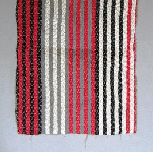 """Randigt vävprov, möbeltygsprov, i svart, rött, vitt och grått. Ett kraftigt och stelt möbeltyg vävt i korskypert med inslagseffekt på rätsidan. Varpen är av tunt tvåtrådigt bomullsgarn i ljust grått. Inslaget är entrådigt lingarn vävt med tre trådar tillsammans. Ränderna är centimeterbeda och grupperade i bårder med följande kombinationer:halvblekt/rött, halvblekt/svart, rött/grått, grått/halvblekt, svart/rött. Det är sju ränder i varje bård.  En pappersetikett är fastknuten med lingarn i ena kortsidan på vävprovet.Texten lyder:""""Radar, Kval.:Bomull lin iinslag, Pris: 520:-"""". Det är en tryckt spånfågel med texten: """"SKARABORGS LÄNS HEMSLÖJDSFÖRENING SKÖVDE-LIDKÖPING"""" på den andra sidan av etiketten.  Vävprovet med modellnamn Radar är formgivet av Ann-Mari Nilsson och tillverkat av Länshemslöjden Skaraborg. Vävbeskrivningen har varit publicerad i Tidskriften Hemslöjden nr 4 1987. Se även inv.nr. 0125,0127-0131 Vävprov och Möbelklädsel i olika färgställningar och material."""
