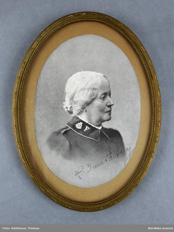 Porträtt av äldre dam iförd uniform. Bröstbild, närmast helprofil, vänd åt vänster.