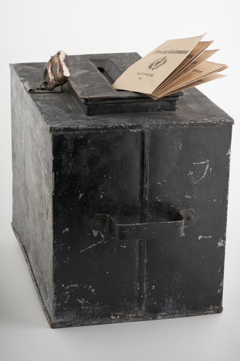 En svart stemmeurne med 10 valgkonvolutter.   NAV-samlingen er en gruppe av gjenstander som har vært anvendt på sosialkontoret (Aetat - NAV) i Skedsmo kommune.