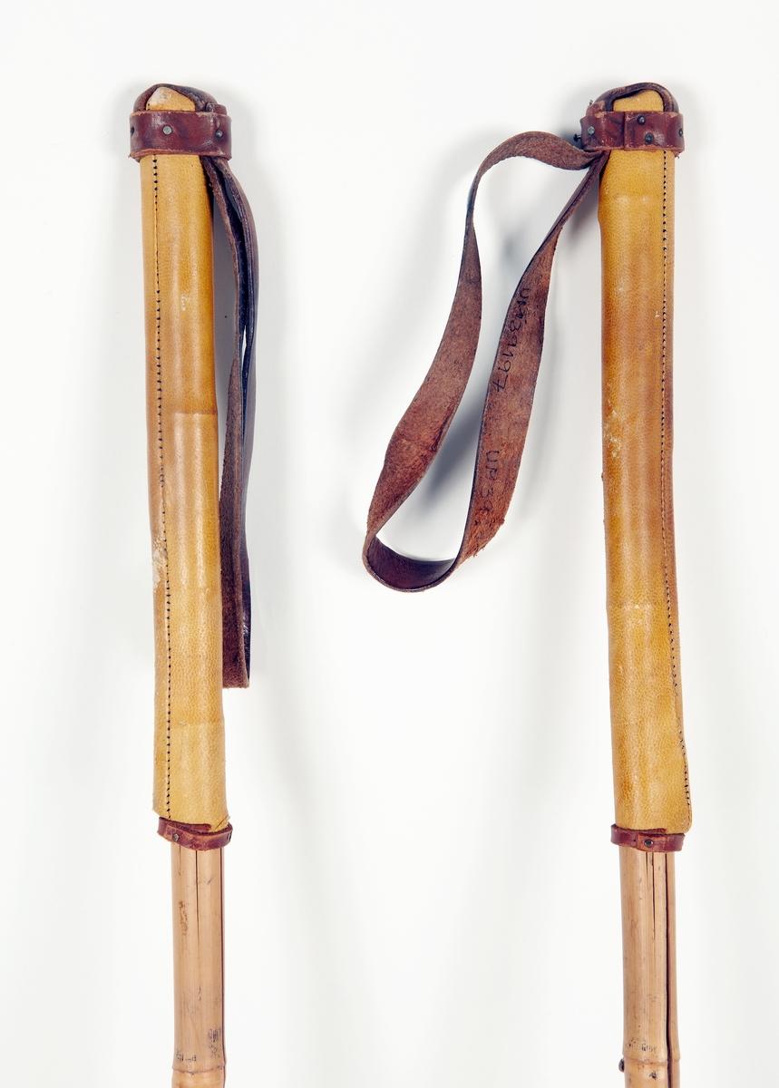 Ett par skidstavar av bambu med holk av lättmetall och järndubb, rottingkringla med korslagda läderremmar fästa vid en metallring. Greppet lindat med läder, handrem av läder nitad med kopparstift.