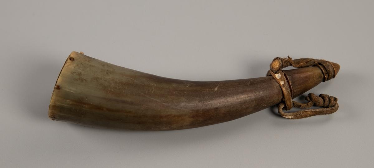 Lite horn i grått og brunt med en liten spiss propp som er bundet til hornet ved en lærrem. Oval topp dekket av et flatt trestykke, med små stifter langs kanten.
