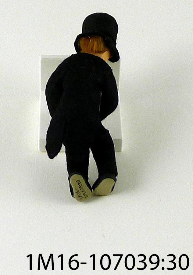 """Docka, brudgum  i svart frack, vit skjorta, hög svart hatt, svarta skor.  Brudgummen håller en vit tygbit i handen. Målat ansikte på tyg, ljusbrunt hår. Tillverkad av Anna Rönne.  Enligt det papper som dockan varit invirad i som förvaring står det """"Ett brudpar (släktingar) det skulle blivit bröllop å """"Kråks"""" men nu får mina efterblivande göra det."""""""