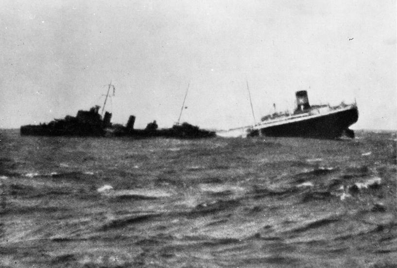 MT ARNE KJØDE (bygget i 1938) synker etter torpedotreff utenfor Hebridene, 15. november 1939. Til venstre et britisk eskorteskip som plukker opp overlevende.