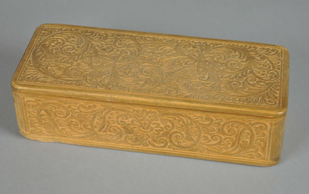 Eske av tre, med hengslet lokk. Esken har rektangulær form med avrundede hjørner. Lokket er hengslet med plugg. På lokk og korpus av esken er det treskjærte, tynne akantusmønstre. På undersiden av esken er det skåret sjakkmønster.