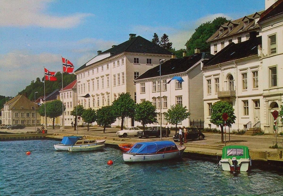 Arendal rådhus t. h. med to flaggstenger med flagg, tre plastbåter ved bragga i forgr.