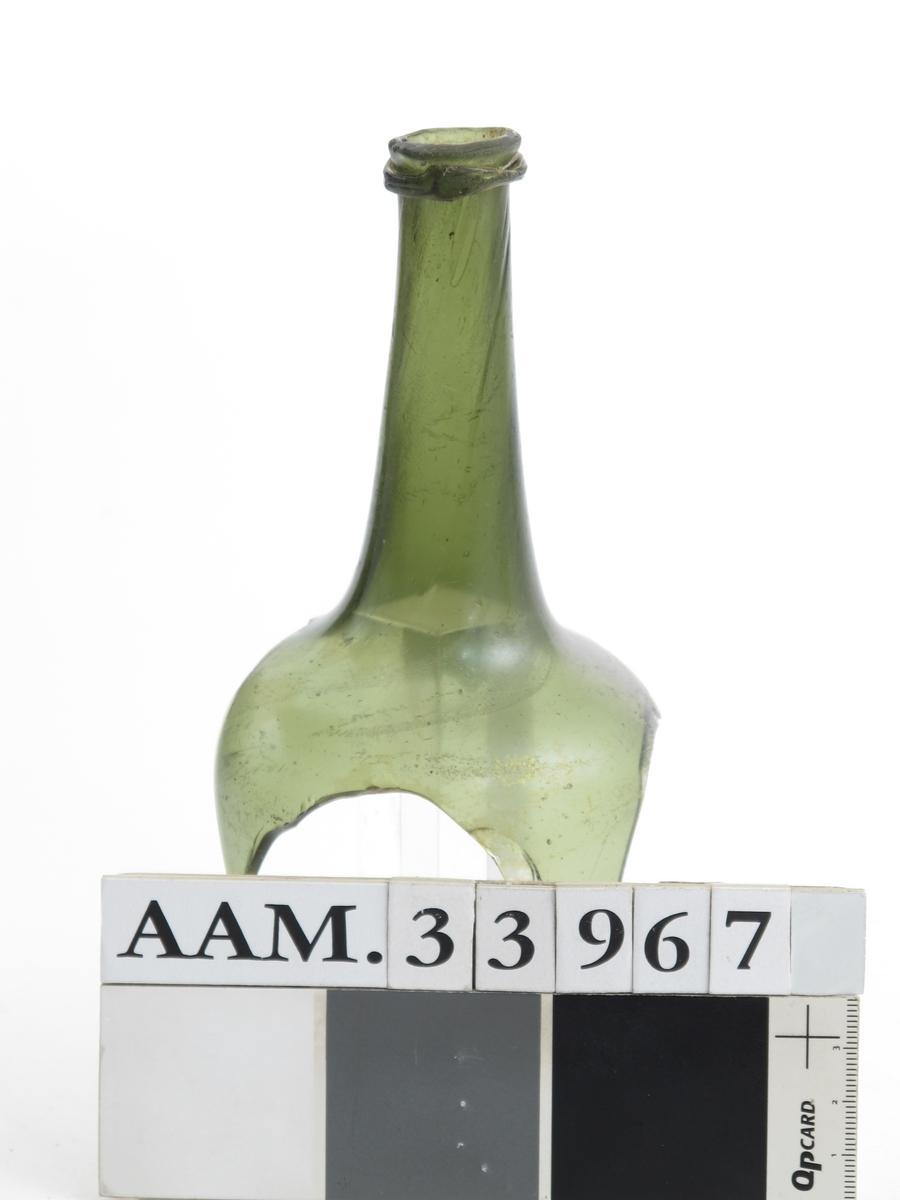 Flaskehals av  butelje, med kork.  Grønt   glass.    Litt av rund skulder, bred  hals, litt skrå.  Kraftig skrå munningsbrem.