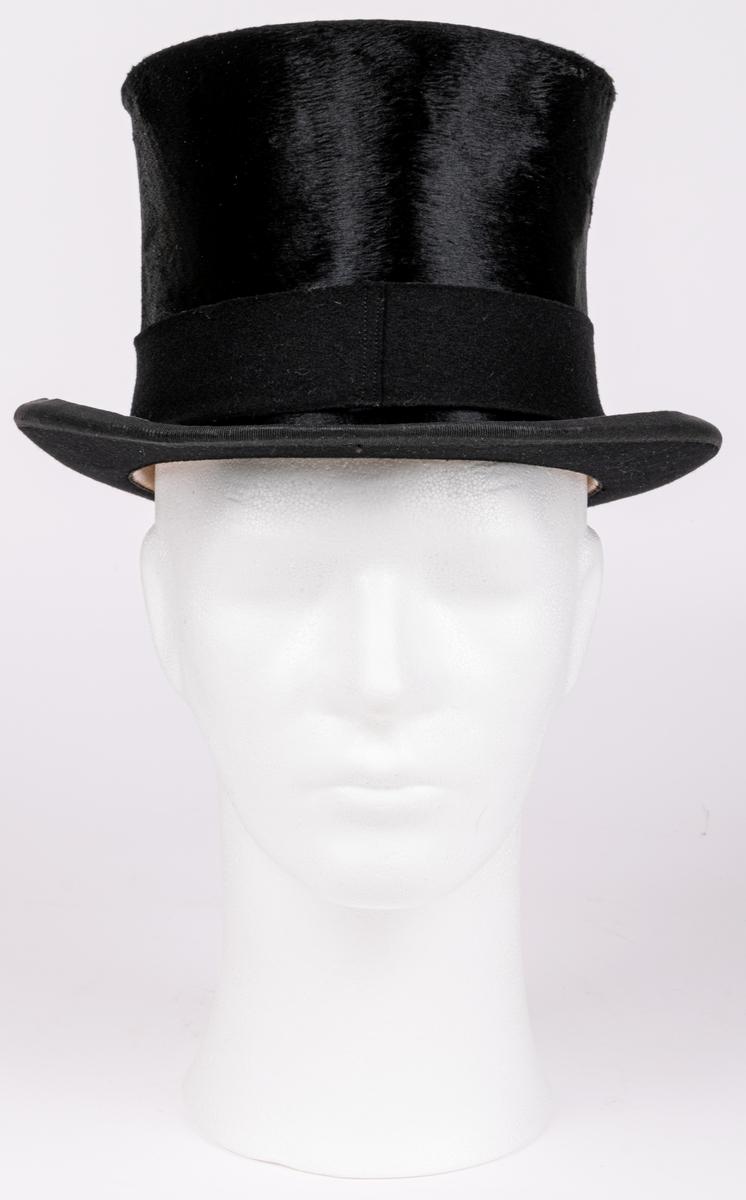 Stormhatt märkt Aktiebolaget J.W Haglund, N. Kungsgatan 1, Gefle. Svart. Höjd 14cm, brättbredd 4,5cm. Hattask av svart papp med guldtext på locket. English manufacture of hats. Best London deposed.