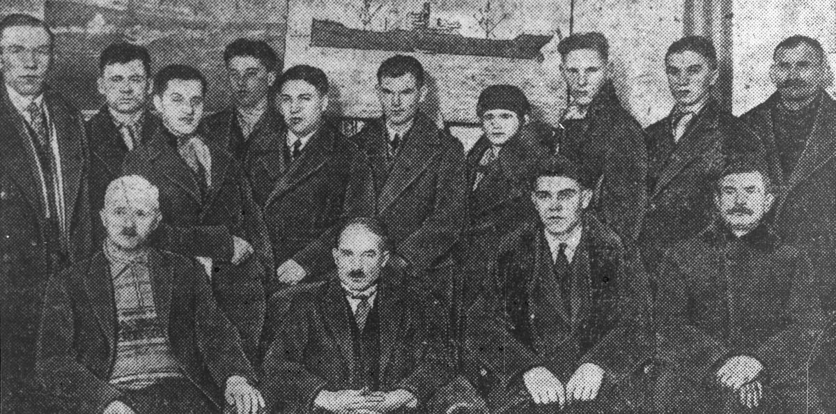 Avfotografert avisfoto av en gruppe menn iført frakker. Bildet er tatt innendørs, med to skipsportretter i bakgrunnen.