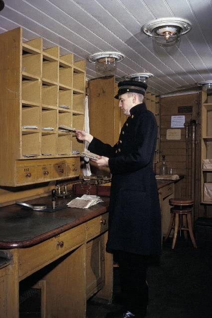 Seriebild ;M 25. I en ålderdomlig järnvägspostkupé, i Järnvägsmuseum i Tomte-boda i Solna, arbetar en postiljon med brevsortering. I den arrangerade situa-tionen agerar fotobiträdet Gunnar Svensson, Postens Fotografer, i en uniform från Postmuseum.