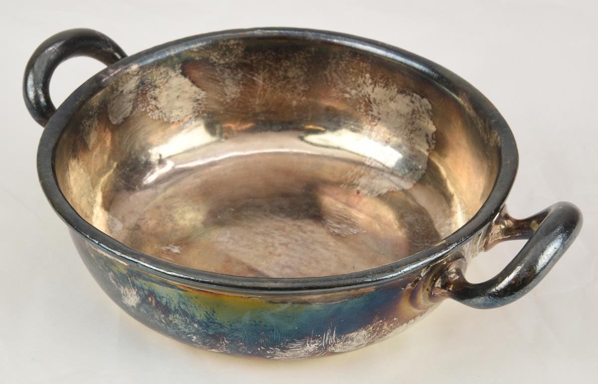 """Rund skål eller karott, av nysilver med ovala handtag på båda sidor, märkt """"TR"""" på undersidan av skålen."""