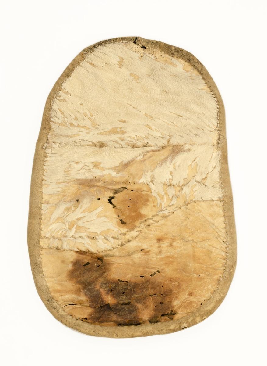 Kjolsäck från Svärdsjö.  Form: äggformig, något sned. Framstycket avslutas upptill med en liten tunga.  Framsidan och åtsidan på bakstycket av svart vadmal. Bakstycket av hårbesatt vitt kalvskinn. Fodrat med vitt tuskaftlinne. Dekor. Applikationer i rött, grönt och gult (vitt?) vadmal, s k renhornsmotiv. Appl. påsydda medelst en kant av tenntråd. I en av applikationerna ett årtal i gul vadmalsappl '1713' (1718?). Bakstycket märkt med korsstygn i rött '1855' och 'B? HD'. Inköpt 1912.
