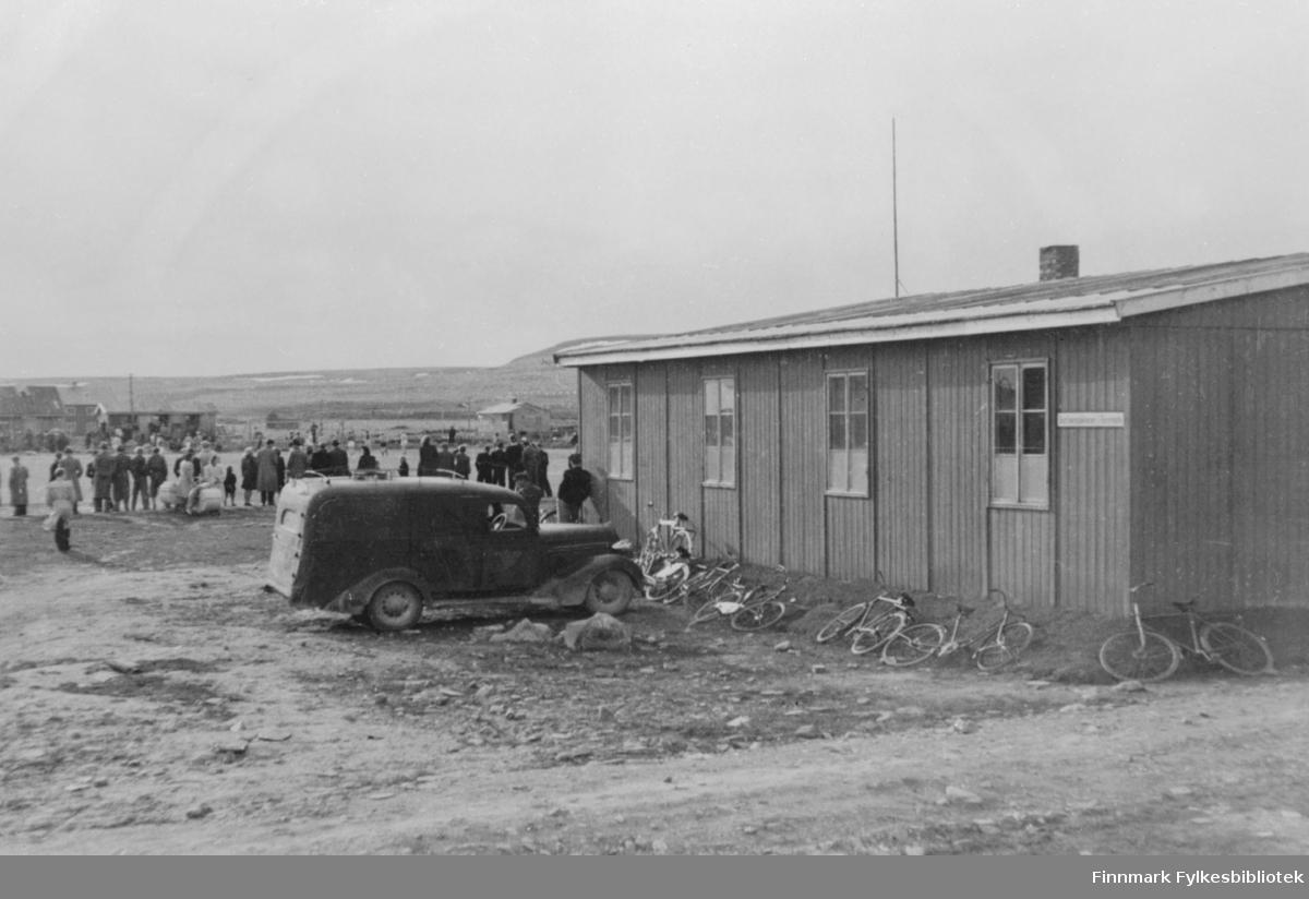 """Bildet viser """"Fotballkamp i Vadsø"""" i 1945. Publikum sees i bakgrunnen, noe av fotballbanen. Kontorbrakke i forgrunnen. Sykler og en parkert bil."""