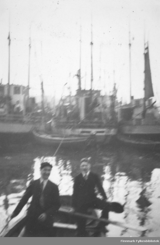 Vardø havn 1933. Harald Haug og Arne Klemetsen sitter i en liten robåt midt i havna i Vardø. Familiealbum tilhørende familien Klemetsen. Utlånt av Trygve Klemetsen. Periode: 1930-1960.