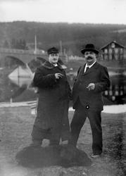 To menn og en hund foran bru over elva. Til venstre: Doktor