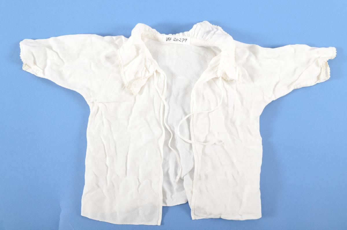 Barne skjorte i kvit flanell. Open bak med knyteband. Rund rynka krage med smal hekla kant. Sammanhengande saum i ermet og sida. Maskinsydd.
