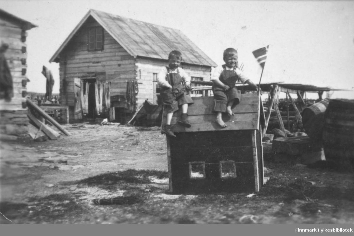 To gutter sitter på taket til et lekehus i Salttjern. Kanskje det er 17. mai siden Norsk flagg er med?