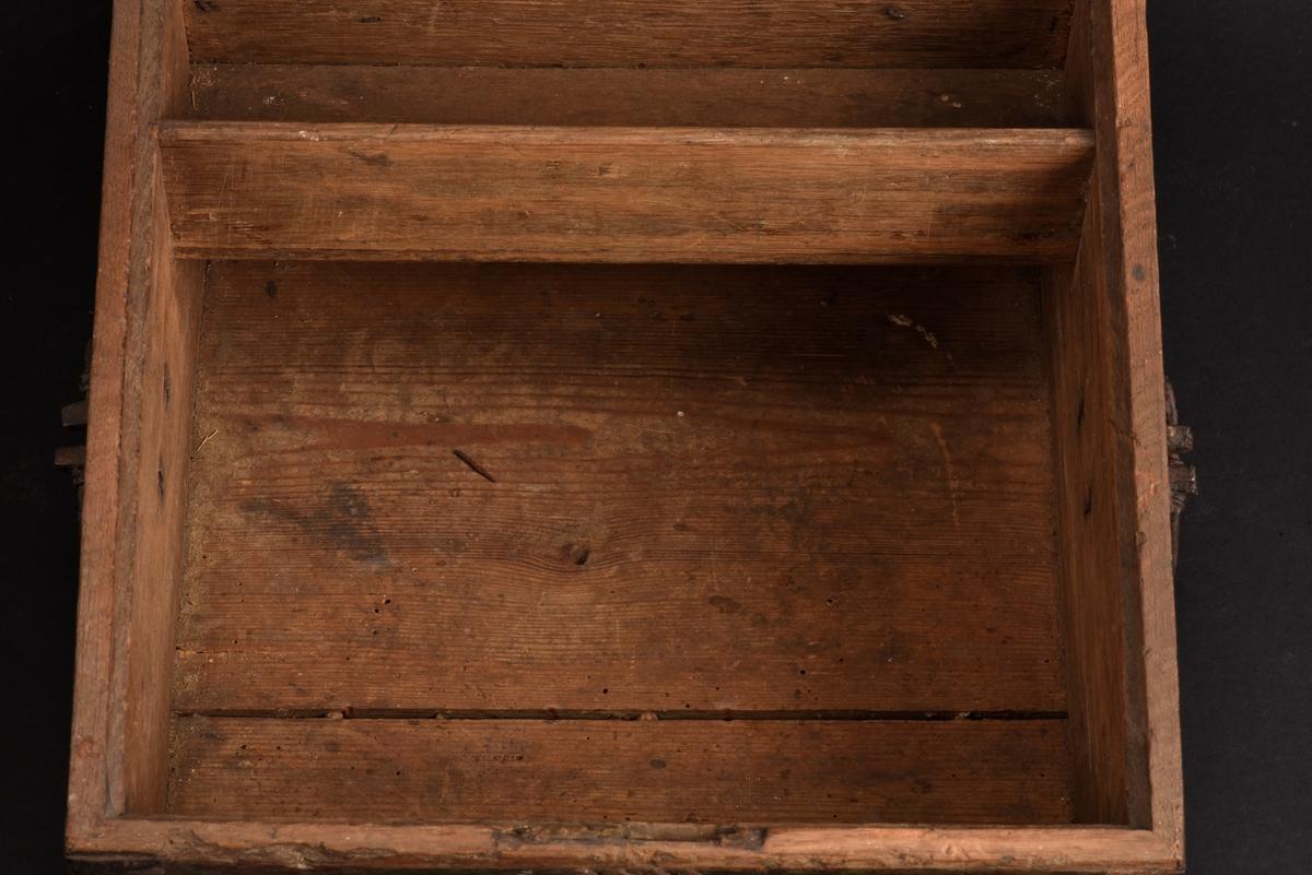 Rektangulärt, grönt skrin med pulpetlock tillverkat av ek. Smidda beslag och gångjärn, som är svartmålade. På sidorna och framsidan en utskuren spegel i relief. Utsirade hörnbeslag och nyckelskylt som är utformad som en utdragen triangel. Inuti ett fack utan lock mot bakstycket.