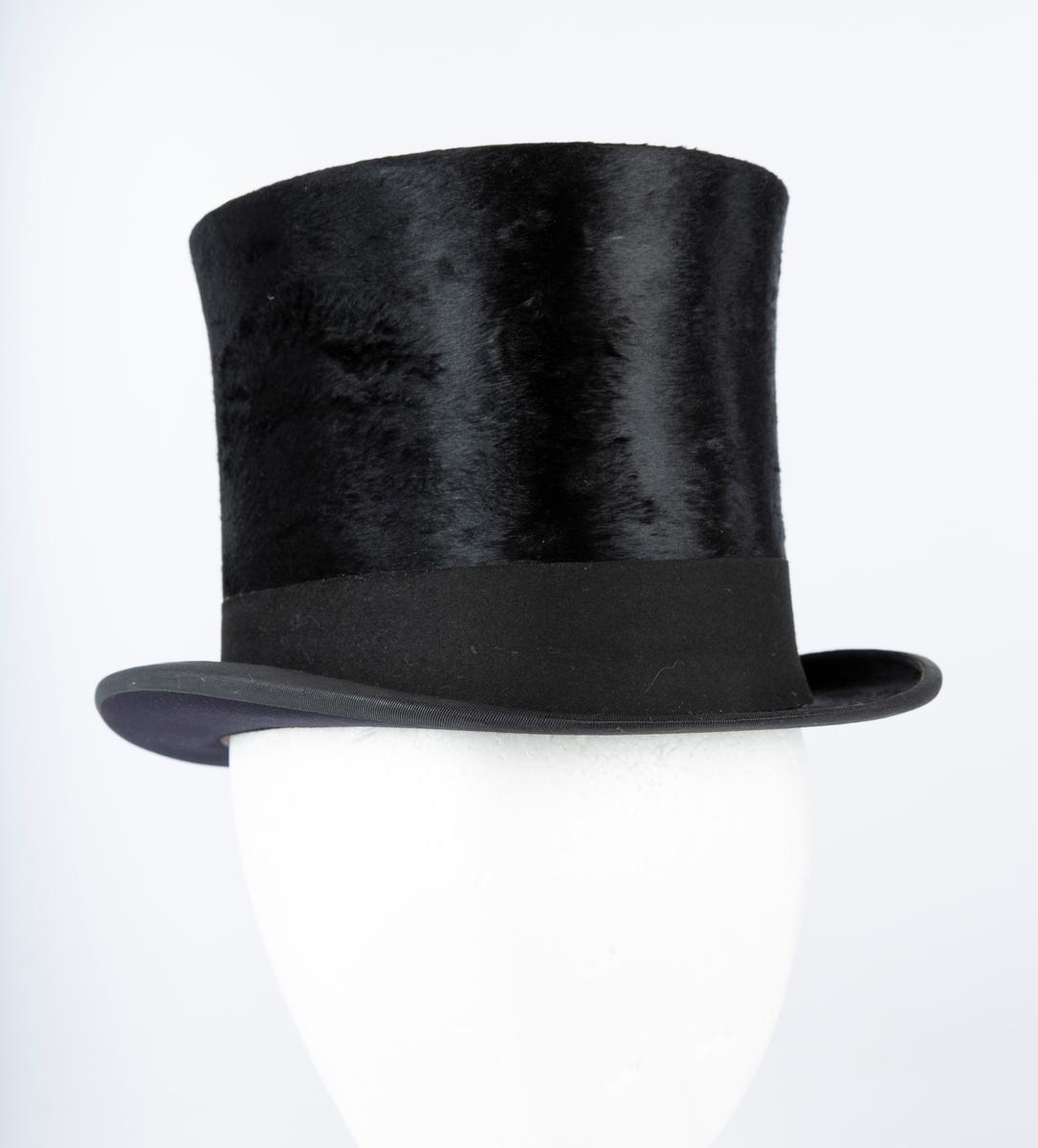 Oval hatt, rett pull med flat topp, flosset stoff, matt hattebånd. Flar brem forran og bak, oppbøyet sidekant. Foret med brun ripssilke. Svettekant i skinn. Inni hatten et visittkort  med påskrift J. Schaan Theiste, Burauchef   største LlxB: 30x24  Innvendig mål: L 20  B 15  H 15