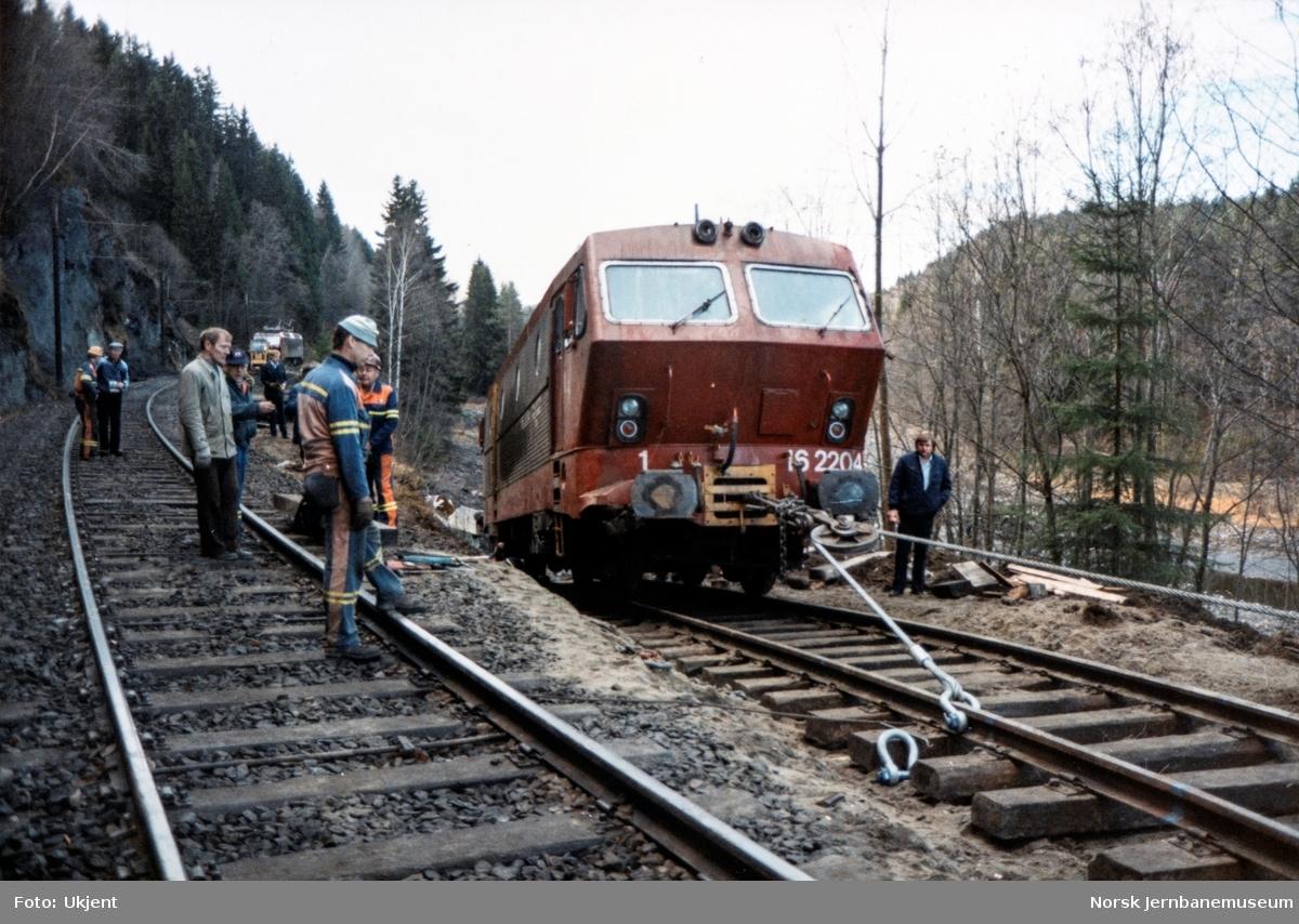 Avsporet og veltet elektrisk lokomotiv El 16 2204 etter å å kjørt inn i et jordras. Lokomotivet fikk store skader, men ble berget og reparert. Her trekkes lokomotivet opp på hovedsporet av diesellokomotiv Di 3 626