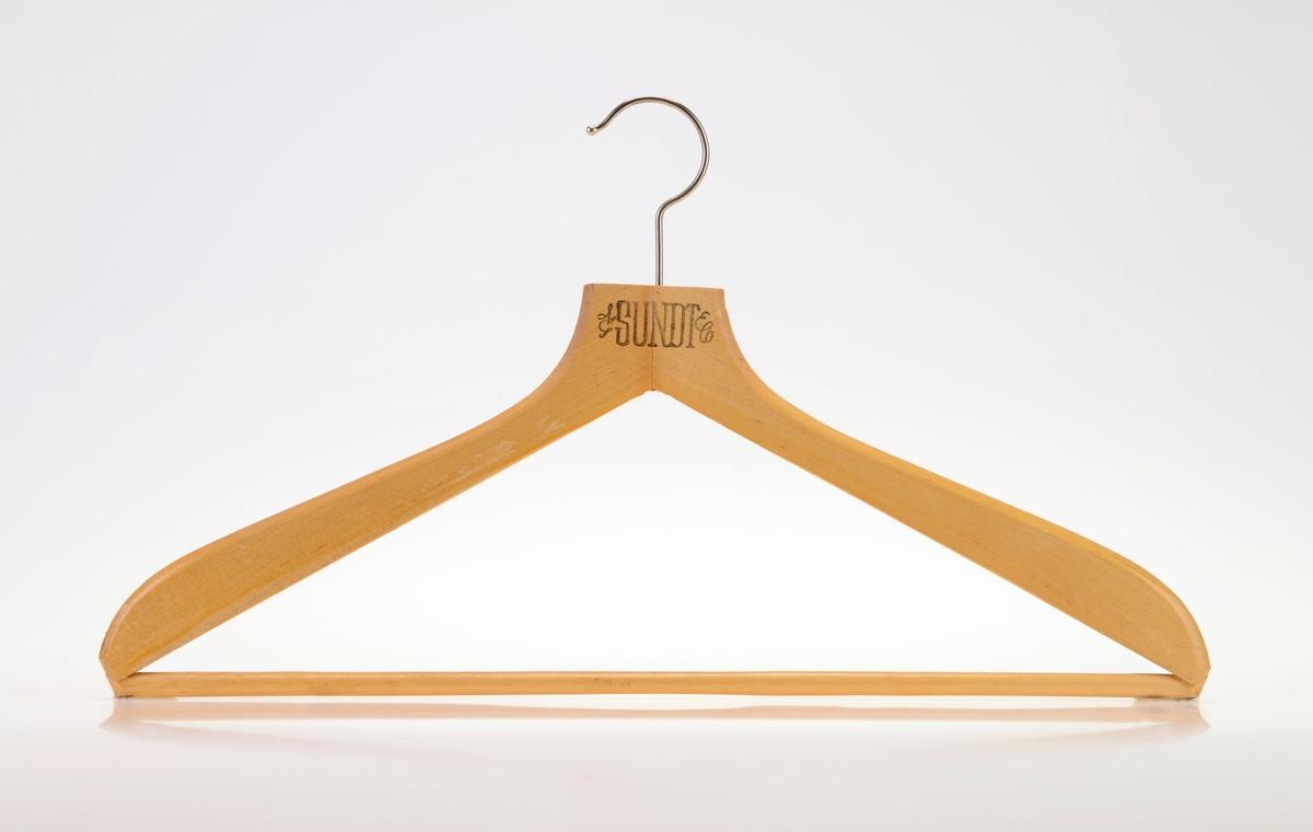 """En kleshenger i tre med to armer med stang i mellom slik at man kan henge klær på både armene og på stangen. For oppheng er det en enkel krok i metall. Det er tekst på den ene siden av kleshengeren, se """"Påført tekst/merker""""."""