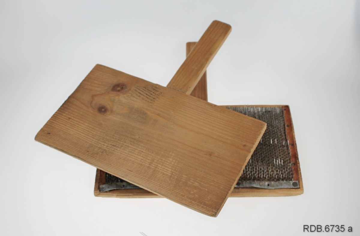 Et par ullkarder laget av tre, ei rektangulær plate med skaft. På innsida av plata er fastspikret ei metallplate med lange pigger. Brukt til å karde saueulla med før spinning. Kardene framstår som reine og ser ikke ut til å ha vært mye brukt.