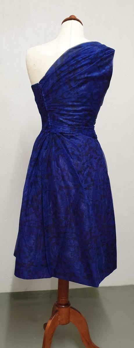 Blå kjole av silke med en skulder, rynket i siden. Moderat lengde skjørt, rynket i siden og i ryggen mot glidelås. Til kjolen følger det med et underskjørt av silke.