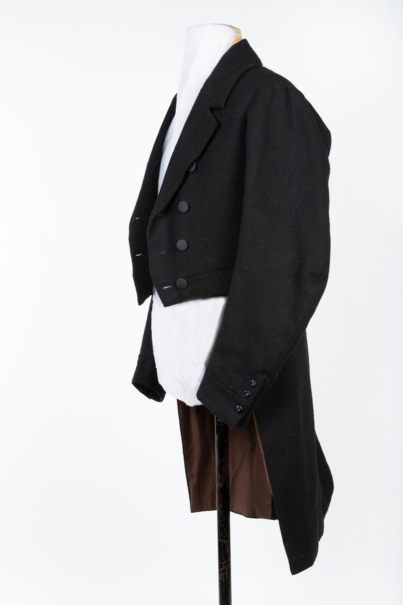 """Kjole eller frakk av ull til Follo mannsbunad.   Figursydd. Laget i svart, toskaftvevet ullstoff, foret med lin- og bomullstoff og vattert.. Den er rett avskåret i livet foran, og har knelange skjøter bak. I ryggen midtsøm og to buede sidesømmer. Nederst markerer en knapp på hver sidesøm livlinja. Skuldersømmene er trukket bakover. Kjolen har nedbrettet krage og brede slag. og er dobbeltspent med svarte trukne stoffknapper, 5 sett knapper, 3 sett knapphull.. Ved hver ermesplitt er er tre små svarte metallknapper og i skjøtene bak er det skjulte lommer.  I skriftlige kilder opptrer """"kjol"""" hyppig, gjennom flere hundre år. I de første tiåra av 1800-tallet beskriver dette et plagg som ligner det vi kjenner som kjole i gallaantrekket kjole og hvitt. Kjolen til bunaden er kopiert etter tilsvarende plagg fra Gaavim i Kroer, Ås.  Drakten er en rekonstruksjon av antrekk etter Ole Gaavim (1774-1842) fra Gaavim, Kroer i Ås. Bunaden er sydd på dugnad av Komiteen for Follo Mannsbunad assistert av bunadsskredder. Bunaden er en gave til Follo museum.  Knelange skjøter, fôret med lin og bomull."""