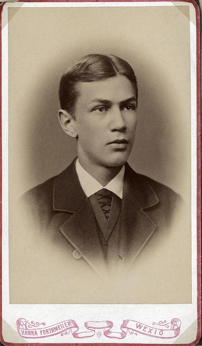 Porträttfoto av en ung man i mörk kavajkostym med väst m.m.  Bröstbild, halvprofil. Ateljéfoto.