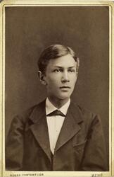 Porträttfoto av en ung man i mörk kavajkostym med väst m.m.