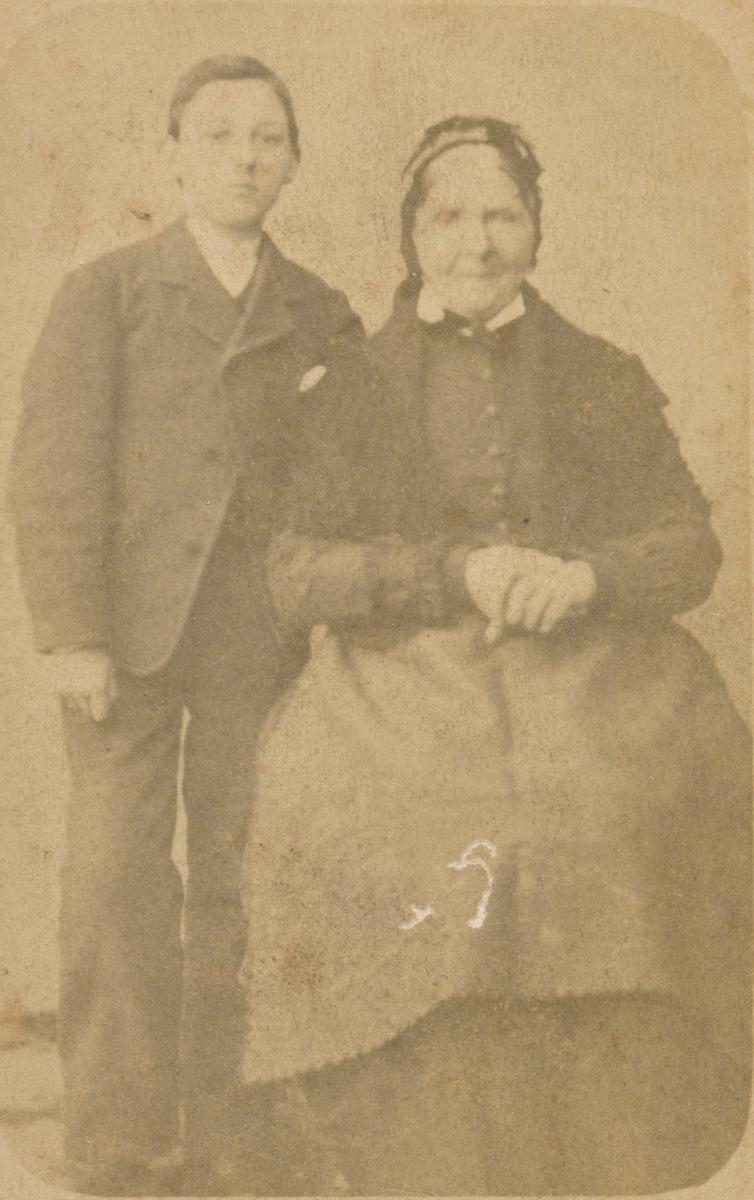 Bildet viser en voksen sittende kvinne og en ung gutt som står ved hennes side, ukjente