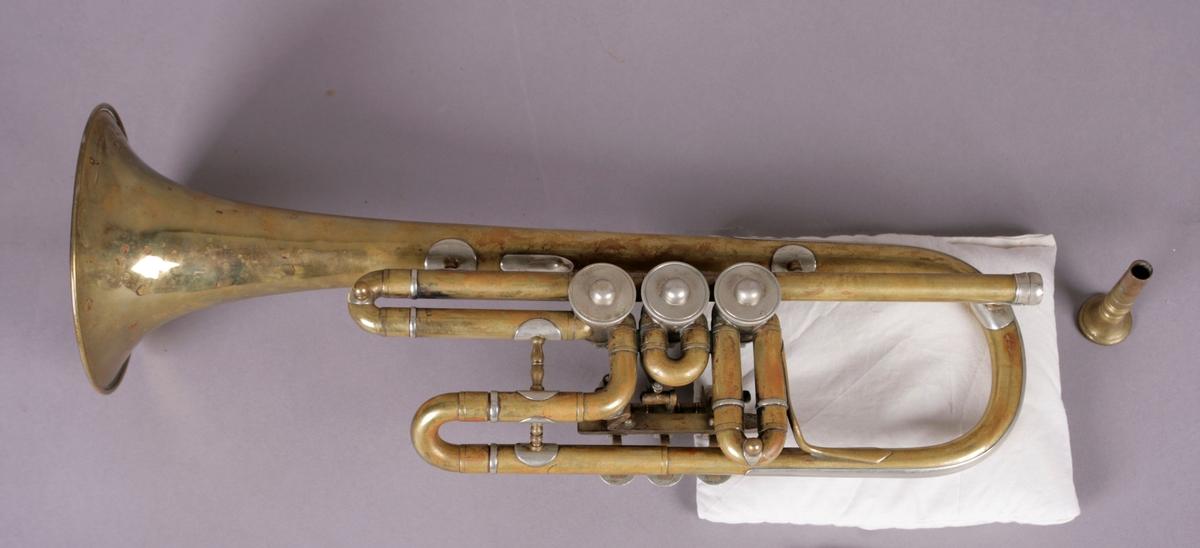 Trompet i D med tilhørende munnstykke.   Utrustning: Stemmebøyle som i formen ligner ventildragene. Ventilbøyle i første og tredje ventil kan trekkes ut. Fem støtter i dreid helmaterial og rund fot, en c-formet støtte for venstre hånd mellom klokkstykke og tredje ventildrag. Nysølveførstærkning ved klokkstykksbøyle.  Mekanikk: Tre dreieventiler og tommeltrykkverk, runde trykkplater og «Hufeisenanschlag» i rekkefølge: heltone, halvtone, en og en halvtone. Særlig interessant er at trompeten har et påfallende stort klokkestykke for å være en D-trompet. Klokkestykket er nok vanlig størrelse for B-trompet. Rørlengden har kortets for å oppnå d-stemning, ellers virker utganspunktet være en B-trompet, hvilket nok beror på at det var fortsatt uvanlig med D-trompeter. Bruken av disse kom mer og mer med behovet for å kunne spille høye trompetstemmer i barokke partier. Etter hvert ble instrumentene (proporsjonene) anpasset stemningene.