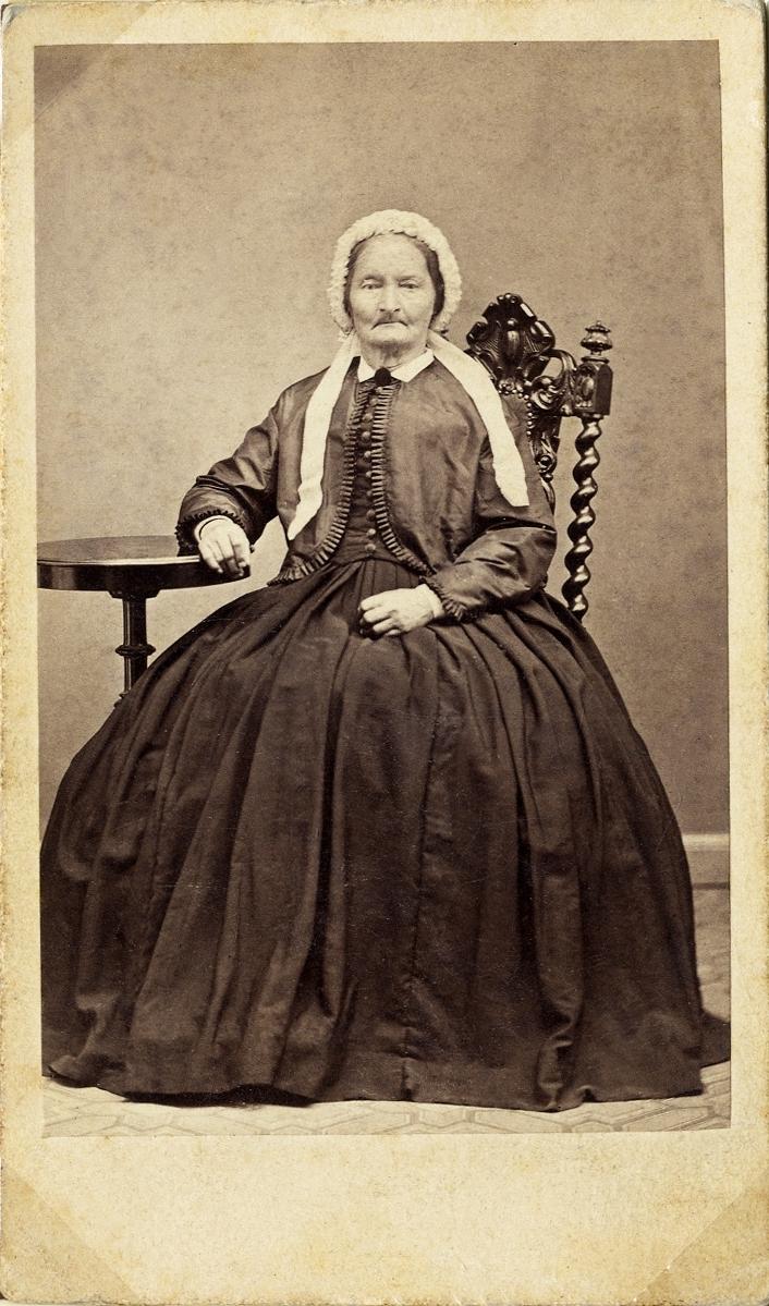 Porträttfoto av en medelålders kvinna i krinolin med jacka och spetsmössa med långa band på huvudet. Hon sitter på en högryggad stol vid ett pelarbord. Helfigur,en face. Ateljéfoto.