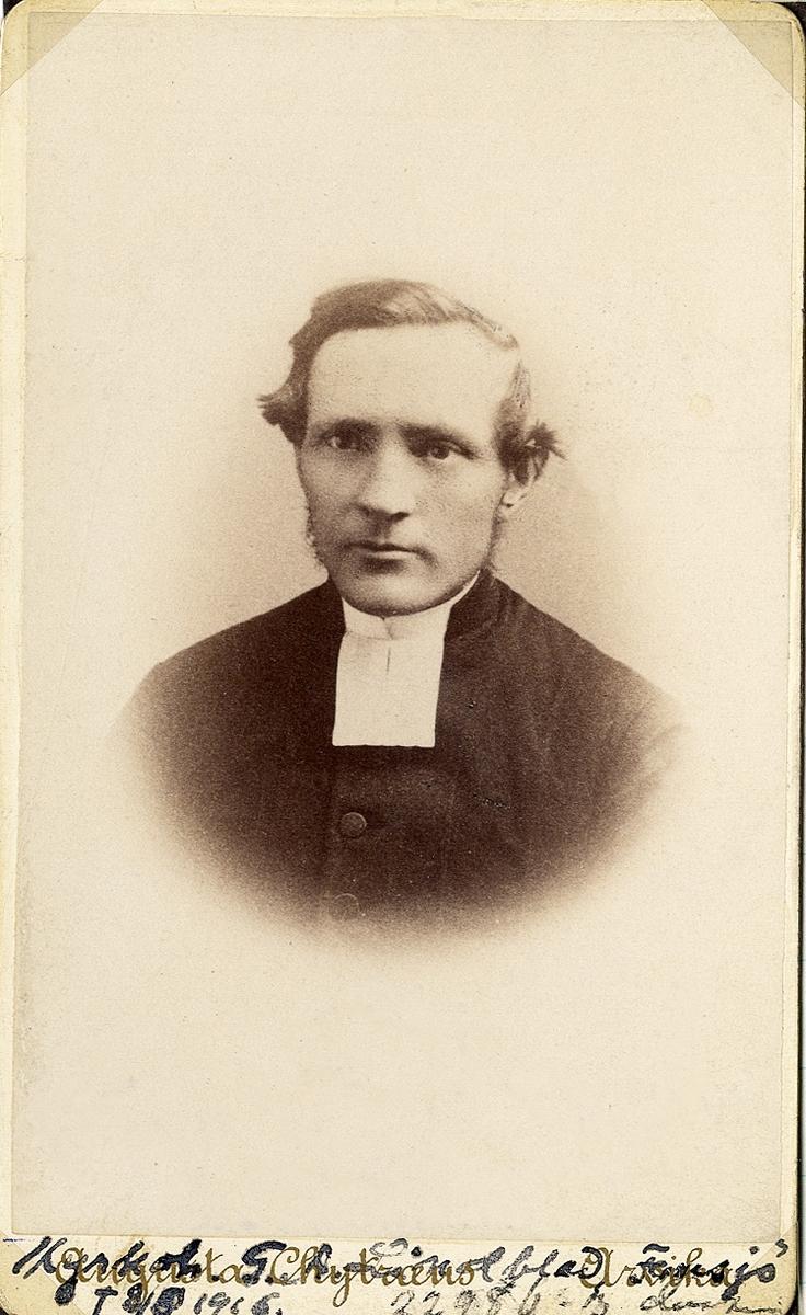 Porträttfoto av en man i prästrock och prästkrage.  Bröstbild, halvprofil. Ateljéfoto.