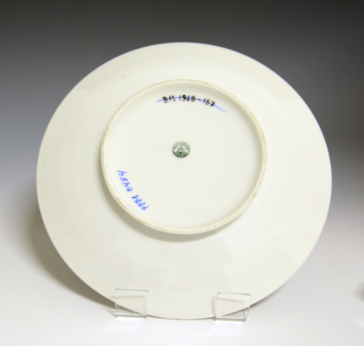 Prot: Tallerken eller lite fat av porselen, med glatt kant. Lav skråstillet fotring og sirkulære riller på speilen og indre del av fanen.