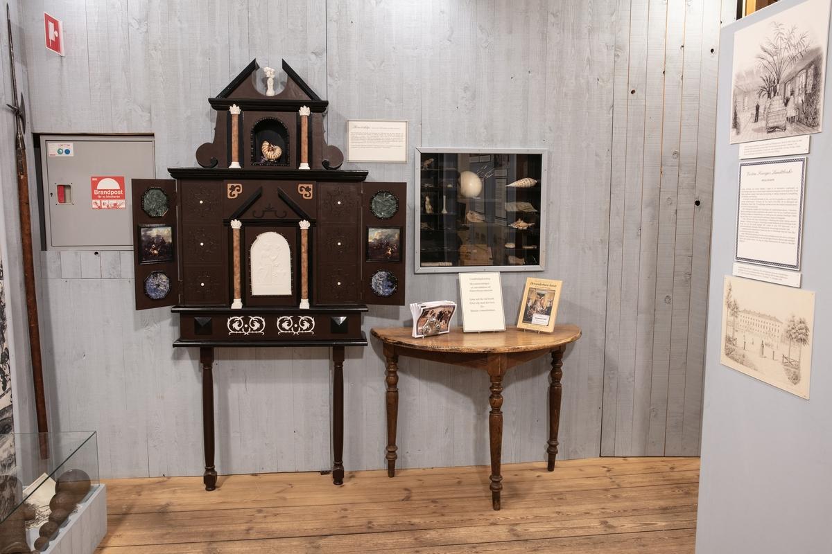 Vänersborgs museum. Mezzaninsalen, konstskåp och bord med utställningskataloger