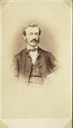 Foto av en man med mustascher, klädd i kavajkostym med väst,