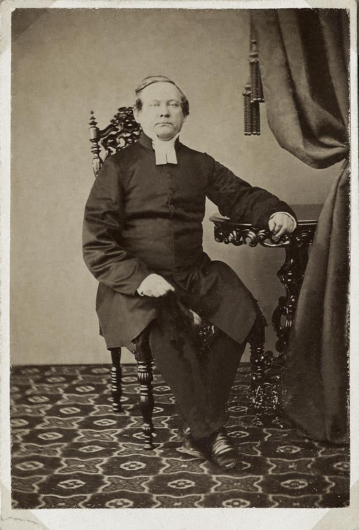 Foto av en medelålders man i prästrock och prästkrage. Han sitter på en högryggad stol och vilar ena armen mot ett  pelarbord i nyrokoko. Till höger syns ett draperi.  Helfigur. Ateljéfoto.