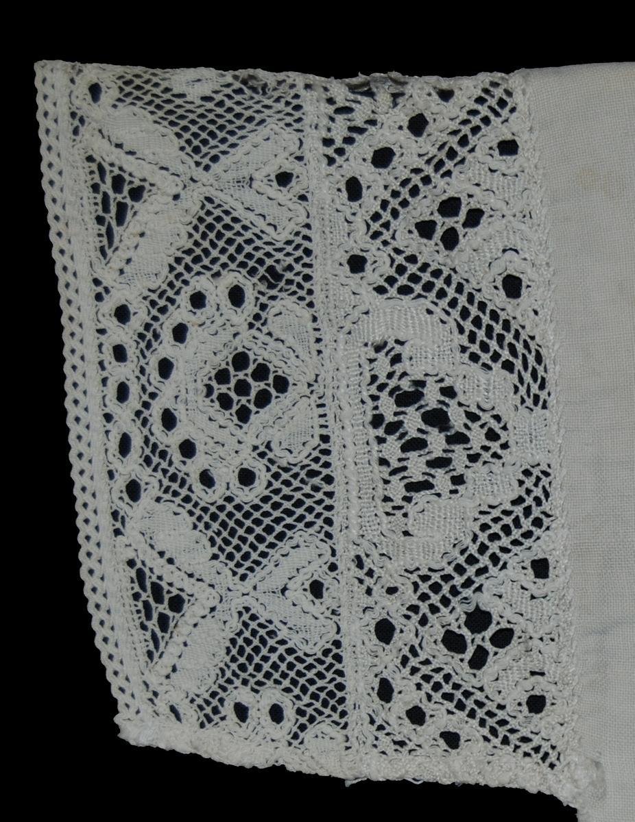 Av vit bomulslärft, rakt stycke med söm mitt bak, hoprynkad ovanför sömmen, ögglor av vit lintråd fastsydda vid nederkanten , bred fåll vid framkanten, kantad med spets, sammanfogad av 2 spetsar, dalknyppling, vit bomullstråd med bomullsgrovände. Spetsens framkant kantad med vita zick-zack vävda bomullsband. Spetsen kortare än hattens framkant. Stort hål på lärften, lagad med lapp fastsydd på rätsidan. Lärften sliten samt hål på vid nederkanten. Pappersetikett med tryckt och med bläck skriven text: Gestriklands hemslöjdsförening spettsutställning, Gävle 1916. Mockfjärdshatt. Nederst: Näckström. Skaftros.   Pappersetikett med tryckt och med bläck skriven text: Gestriklands hemslöjdsförening spettsutställning, Gävle 1916. Mockfjärdshatt.  Pappersetikett med tryckt och med bläck skriven text: Gestriklands hemslöjdsförening spettsutställning, Gävle 1916. Mockfjärdshatt. Spetsens kortsidor kantade av vita bomullsband