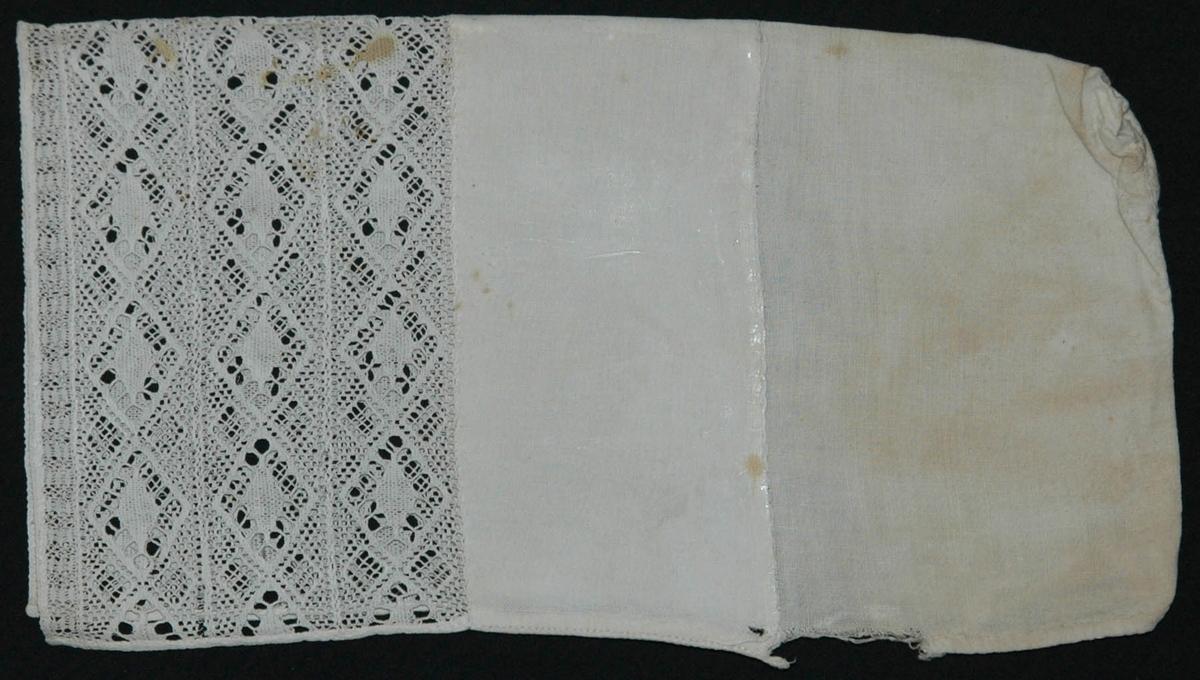 Av vit linnelärft, rakt stycke med söm mitt bak, Bred fåll vid framkanten, kantad med spets, sammanfogad av 4 spetsar, dsen yttre smal, maskinvävda, vit bomullstråd.  Spetsens kortsidor kantade med vita bomullsband. lärften trasig vid nederkanten