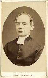 Foto av en äldre man i prästrock och prästkrage. Bröstbild,,
