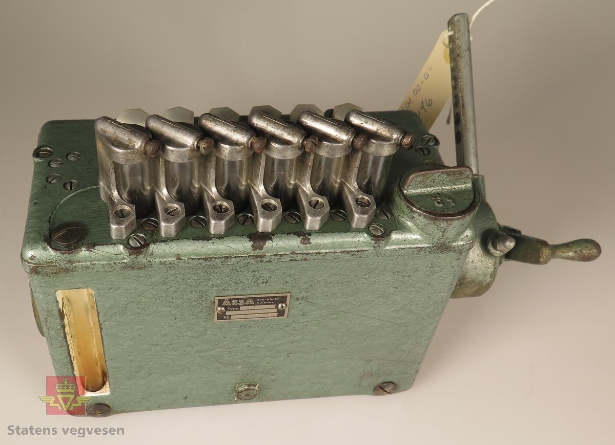 Smøreapparat med sveiv og håndpumpe. Har 6 ut-innganger og 6 måleglass samt måleglass for det totale oljenivå. Lakkert med grønn hammerslaglakk.
