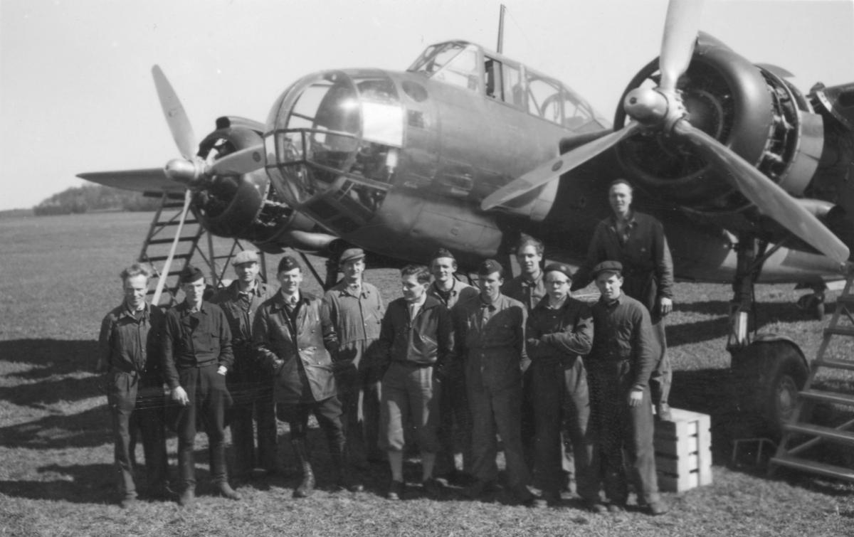 Grupporträtt av flygvapenpersonal samlade nedanför flygplan Saab B 18 efter färdigställd reparation efter haveri vid Fyllebro utanför Halmstad, 1940-tal.