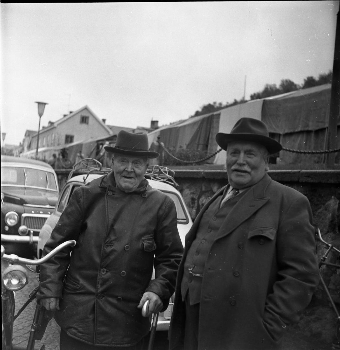 """Två äldre män med och skinnjacka respektive rock står på Brahegatan nedanför torgmuren. Till vänster med käpp i handen står Theodor """"i Sånghem"""" Johansson och till höger David Karlsson. På torget ser det ut att vara marknadstält."""