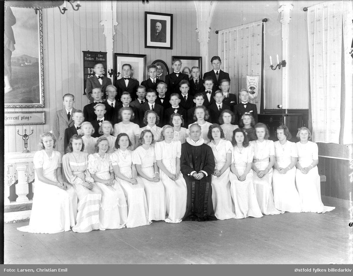 Pastor Kinn med konfirmanter desember 1944 i Sarpsborg. Interiør fra hvilken kirke? Vimpel for Norges Kristelige Ungdomsforbund.