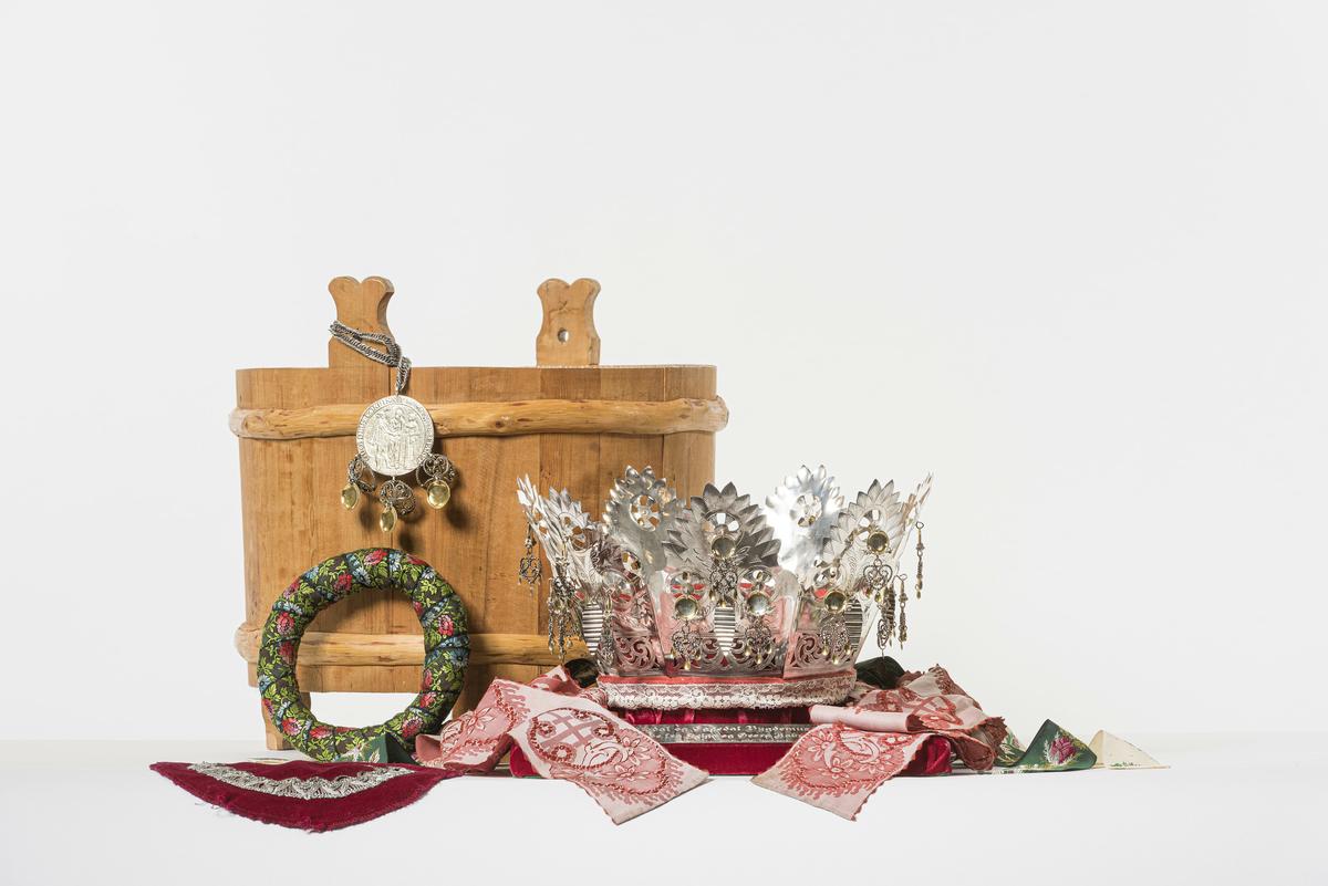 Brudekrone av sølv, loddet sammen av 7 graverte og gjennombrutte sølvplater. På hver plate henger ett riflet løv, samt tre forgylte løv med hjerteformede filigranheng. Krona er polstret innvendig med en ring kledd i rød filt, pyntet med blondekant nederst. Den har 9 nakkebånd av blomstret, brosjert silke, og lange hakebånd av mønstret, lyserød silke.