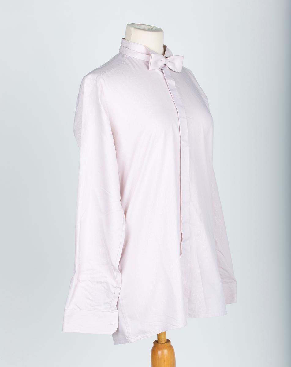 A: Skjorte.   Stående halslinning med liten nedbrettet snipp foran. Dobbelt nakkestykke bak Lang erm med mansjett, skjult knapping. Strukturmønstret stoff. Skjorten har eerreknapping,  B: Tversoversløyfe.  Sløyfe og nakkebånd av skjortestoffet