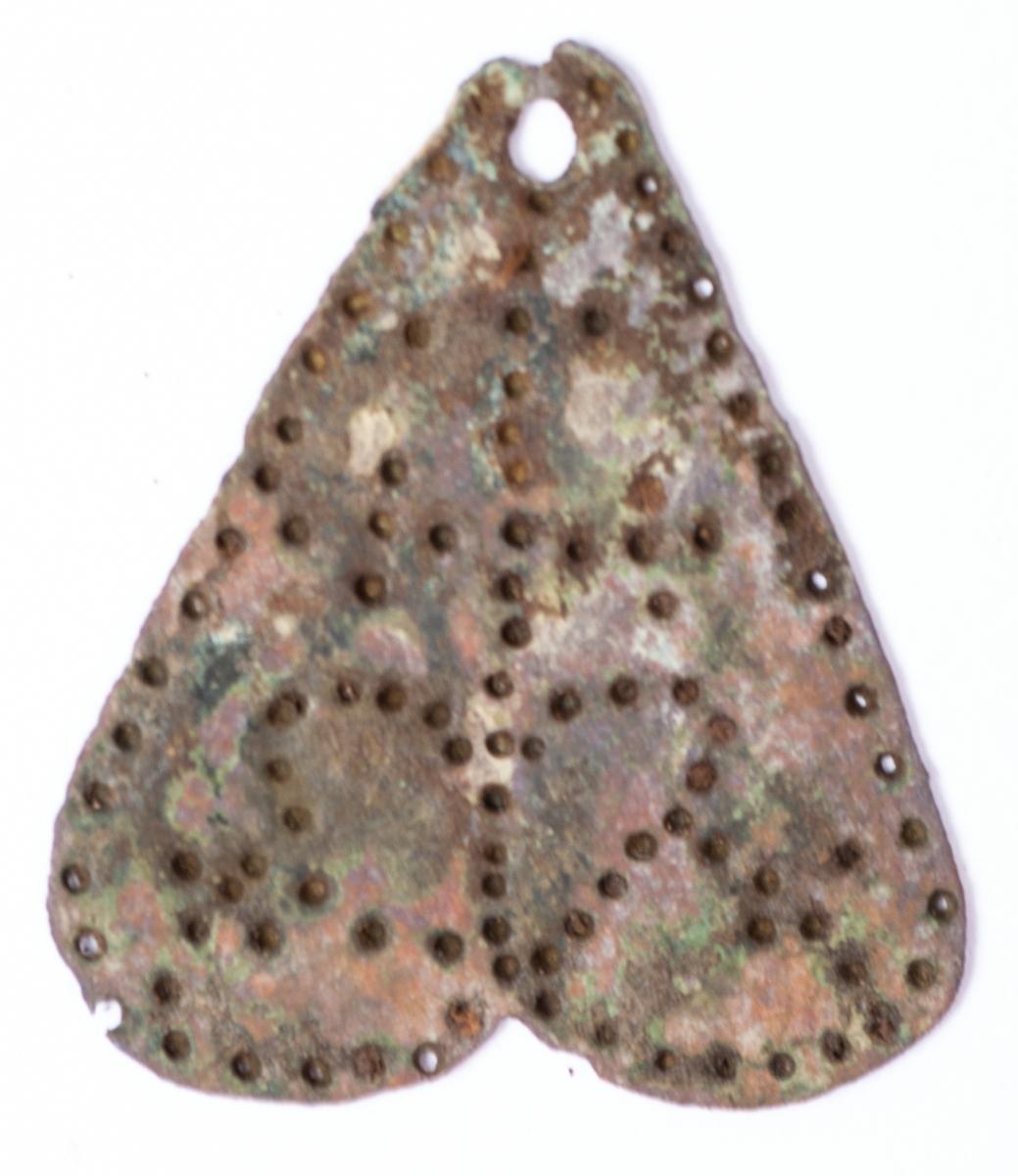 Hjärtformat hänge i kedja av pressbleck. Kan ha suttit under en samisk trumma, enligt tidigare fynd. Se arkeologisk rapport.