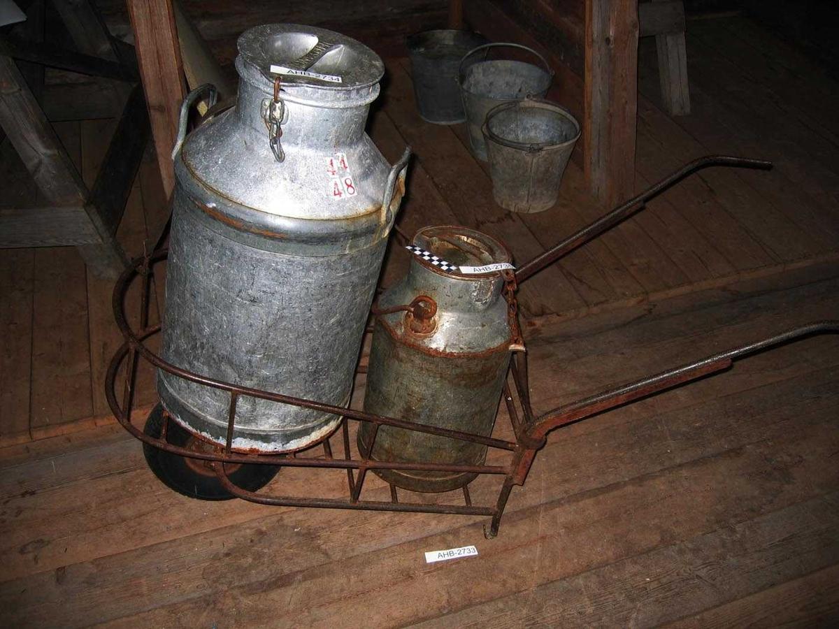 Trillebår med kurv som rommer 2 50 L melkespann. Luftfylt gummihjul. Hele trillebåren er av stål. Spannene er sikret med en lærreim.